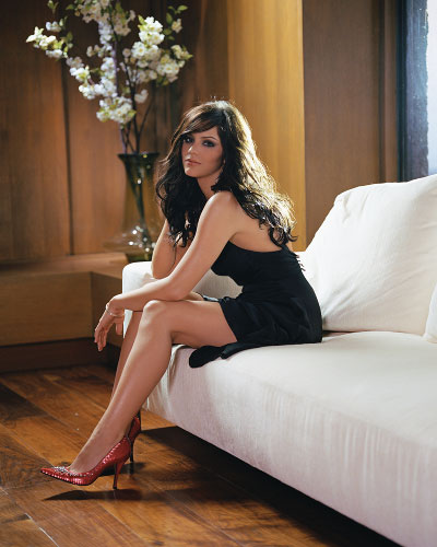 Katharine McPhee sitting on a couch in a black dress